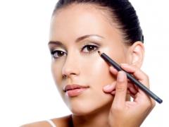woman applying eyeliner on eyelid with pensil